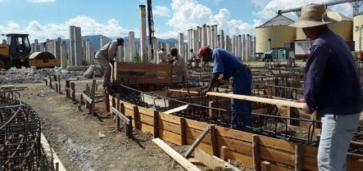 En imagen trabajadores en la construcción de la planta de piensos de Santiago de Cuba