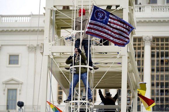 Partidarios de Trump escalaron estructuras metálicas frente al Capitolio este miércoles. foto: Julio Cortez / AP